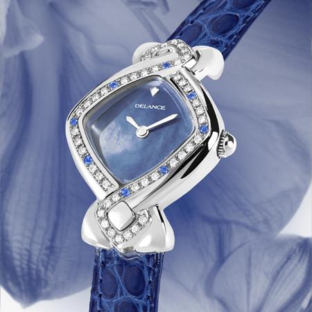 Indira : Montre en acier sertie avec 42 diamants et 8 saphirs, cadran nacre bleue, aiguilles nickelées, cabochon en acier, bracelet en alligator bleu