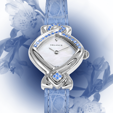 """La montre DELANCE """"Blue Ribbon"""" unit dans la solidarité les femmes du monde entier. Les 28 saphirs bleus célèbrent le cycle de la lune et de la féminité. Vingt-quatre pierres lient l'est à l'ouest en passant par le nord et quatre pierres au sud soulignent la valeur des quatre directions."""