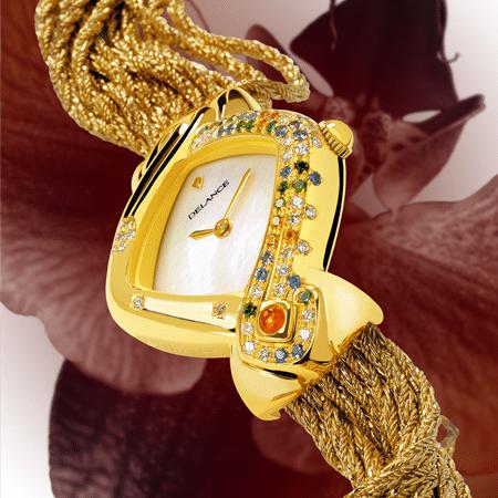 """Pour ses soixante ans, Rina s'est offert une montre DELANCE """"Secret"""" très symbolique. Une montre qu'elle porte comme un bijou symbolique. Les pierres semées à l'est, le futur, 6 oranges + 12 vertes + 18 bleues + 24 blanches, lui rappellent que dans son cœur vit toujours la petite fille créative de 6 ans, la jeune fille pleine d'espoir de 12 ans, la jeune femme idéaliste de 18 ans et la femme enthousiaste de 24 ans. Elle est toutes ces femmes qu'elle fut et bien plus encore. Et parce que mère elle le restera toujours, deux pierres précieuses sont serties à l'heure de naissance de ses enfants."""