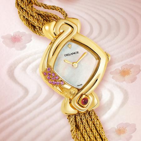 Yuka : Montre en or gravée et sertie de 10 saphirs roses, cadran nacre blanche ou rose, aiguilles dorées, cabochon avec un rubis à 6h, bracelet en brins d'or