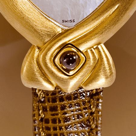 Sofia : Montre de marque en or rose, cadran nacre blanche, aiguilles dorées, cabochon en or avec une opale en feu, bracelet en cuir brun