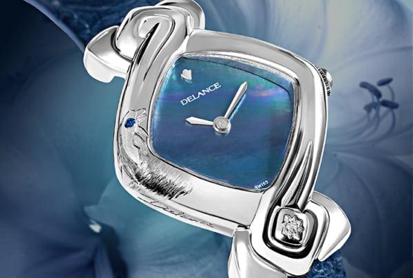 """Un charmant dauphin sortant des eaux est gravé artistiquement sur le côté de cette montre DELANCE """"Dolphin"""". Il semble vouloir plonger dans les vagues bleues irisés du cadran de nacre. Toute de pureté et de simplicité elle signifie, pour la personne qui la porte, son amour de la nature et de la mer. : Montre en acier, cadran nacre bleue, aiguilles nickelées, cabochon en acier avec un diamant à 6h, bracelet en alligator bleu"""