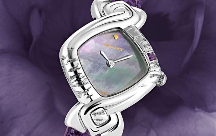 Elle la voulait toute de violet et c'est ainsi qu'elle l'a gravée et sertie d'une améthyste. Pour répondre à la pierre nous avons parée la montre d'un cadran de nacre aux reflets mauves et d'un bracelet en lézard violet. Subtile et délicate, la montre DELANCE «Violet» s'harmonise en tout temps à la personne qui la porte.