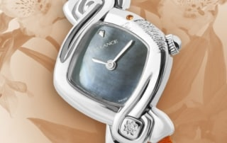 Coraline: Steel watch for a woman with a diamond and hand engraving, pink-orange sapphire at 1 o'clock, blue mother-of-pearl dial, nickel-plated hands, orange leather strap.