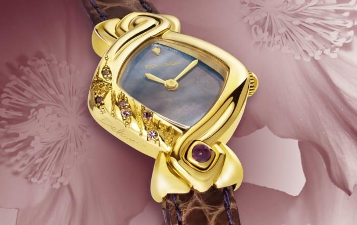 Ulla : DamenGold Uhr mit Handgravur auf der linken Seite und mit 6 Amethysten besetzt, Zifferblatt aus Perlmutt blau/violett, vergoldete Zeiger, Amethyst bei 6 Uhr.